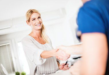Woman shaking hands with team member while checking in at dental office reception desk