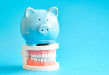 piggy bank sitting on top of false teeth