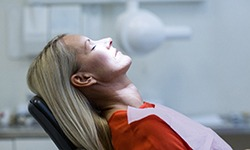 Woman relaxed in dental chair wearing red shirt