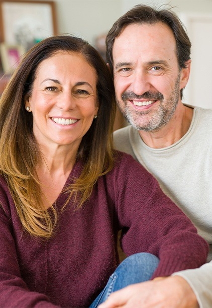Smiling man and woman after dental implant tooth replacement