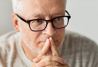 Man in glasses considering dental implant tooth replacement
