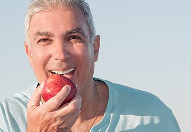 Older man eating red apple