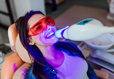 A young female having her teeth whitened in a dentist's office