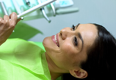 A middle-aged woman staring at her improved smile in the mirror after receiving help from Dr. Graffeo