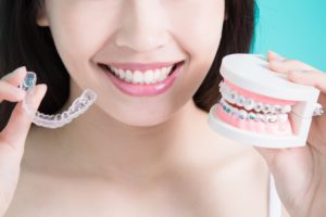 Woman holding model of Invisalign and metal braces.