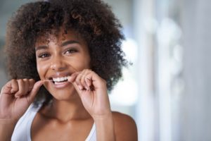 woman flossing for optimal at-home dental care